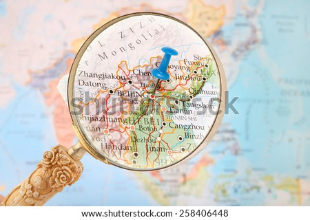 Blue tack on map of Asia with magnifying glass looking in on Beijing, China - stock photo