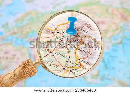 Blue tack on map of Asia with magnifying glass looking in on Islamabad, Pakistan, Middle East - stock photo