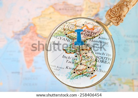 Blue tack on map of Asia with magnifying glass looking in Seoul, South Korea - stock photo