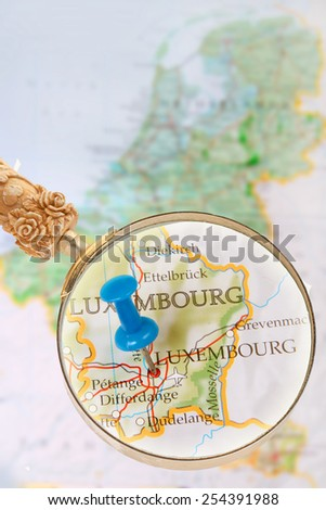 Blue tack on map of Benelux with magnifying glass looking in on Luxembourg, Europe - stock photo