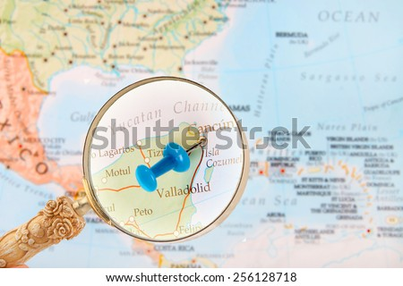 Blue tack on map of Caribbean with magnifying glass looking in on Cancun, Mexico - stock photo