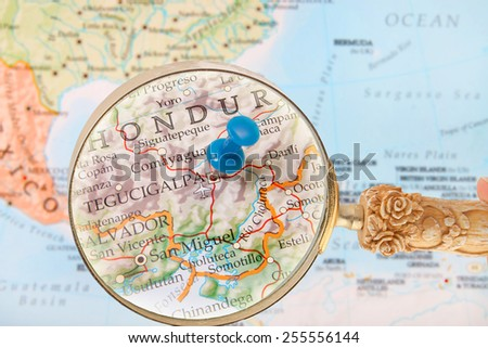 Blue tack on map of Central America with magnifying glass looking in on Tegucigalpa, Honduras - stock photo