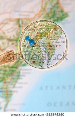 Blue tack on map of Eastern USA with magnifying glass looking in on Washington D.C.  - stock photo