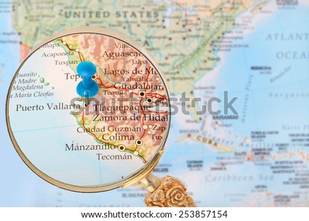 Blue tack on map of North America with magnifying glass looking in on Puerto Vallarta, Mexico - stock photo