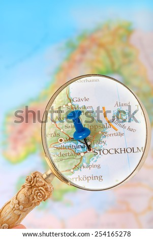 Blue tack on map of Scandinavia with magnifying glass looking in on Stockholm, Sweden - stock photo
