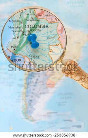 Blue tack on map of South America with magnifying glass looking in on Bogota, the capitol of Colombia - stock photo