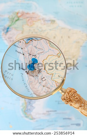 Blue tack on map of South America with magnifying glass looking in on Lima, the capitol of Peru - stock photo