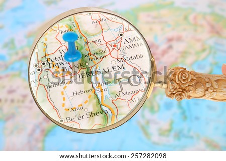 Blue tack on map of the world with magnifying glass looking in Jerusalem, Israel in the Middle East, Asia - stock photo