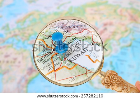 Blue tack on map of  the world with magnifying glass looking in on Kuwait,Iraq, Asia - stock photo