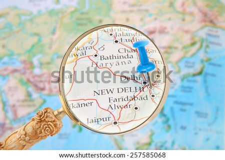 Blue tack on map of the world with magnifying glass looking in on New Delhi, India - stock photo