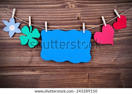 Blue Tag Or Label With Hearts And Flower And Four Leaf Clover On A Line With Copy Space Or Your Free Text Here On Wooden Background, Four Symbols, Vintage, Retro And Old Fashion Style With Frame - stock photo