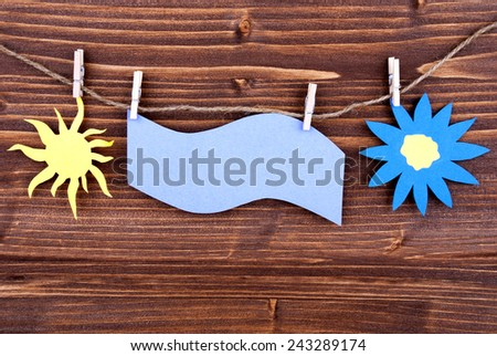 Blue Tag Or Label With Sun And Flower On A Line With Copy Space Or Your Free Text Here On Wooden Background, Two Symbols, Vintage, Retro And Old Fashion Style - stock photo