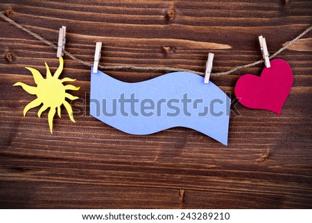 Blue Tag Or Label With Sun And Heart On A Line With Copy Space Or Your Free Text Here On Wooden Background, Two Symbols, Vintage, Retro And Old Fashion Style With Frame - stock photo