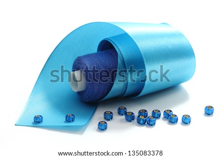 Blue tape, the coil of blue threads and blue  beads on a white background