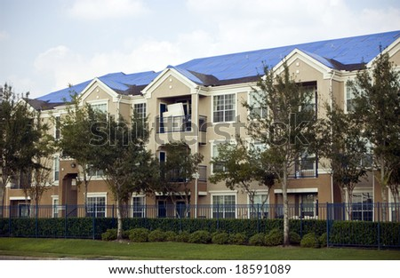 Blue tarps covering the damaged roofs of an apartment complex in the aftermath of a hurricane.