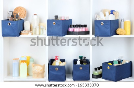 Blue textile boxes with cosmetic products for personal care in white shelves