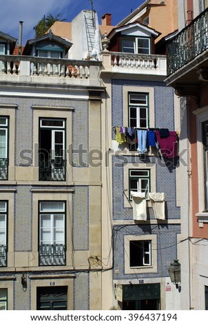 Blue tiled facades of adjacent apartment buildings in Lisbon, Portugal, with laundry hanging on a line in front