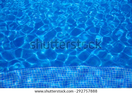 Blue tiles swimming pool water texture background - stock photo