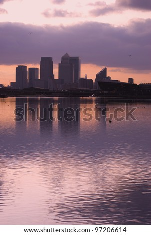 blue tone of canary wharf silhouette over canal at sunset - stock photo