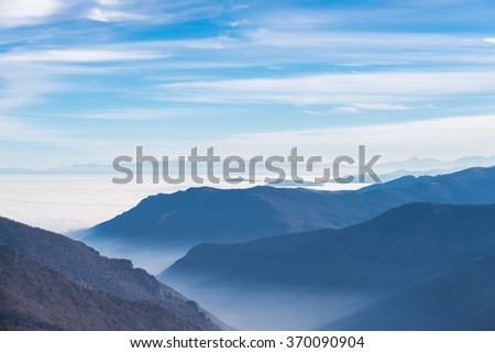 Blue toned distant mountain range with fog and mist covering the valleys below. Soft light and cold feeling. Italian Alps in winter. - stock photo