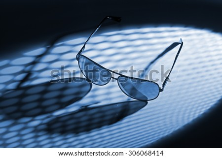 Blue toned photo of sunglasses in dotted light. - stock photo