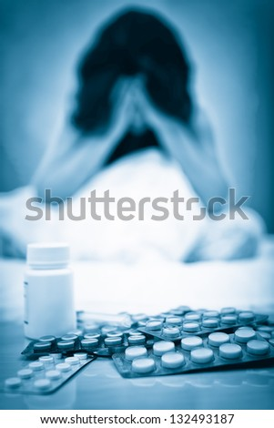 Blue toned portrait of a depressed or suicidal woman with pills on her table