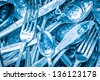 Blue toned silverware being washed with water and detergent - stock photo