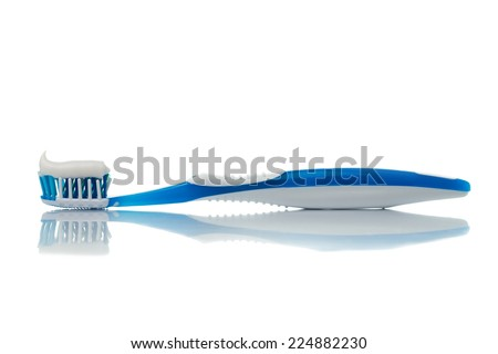 Blue toothbrush with toothpaste on white background - stock photo