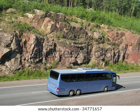 blue tourist bus on rocky highway
