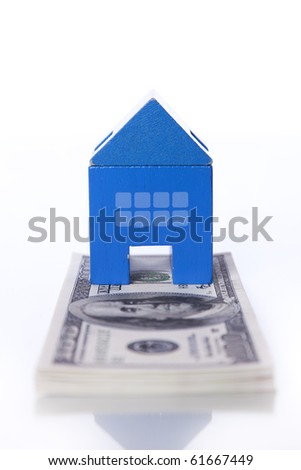 blue toy house over a lot of dollar bills isolated on white  (selective focus) - stock photo