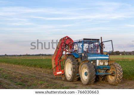 Blue tractor in field shortly before its use, copyspace left