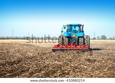 Blue tractor in the field on a sunny day - stock photo