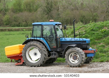 Blue tractor standing idle towing a yellow plastic fertilizer spreader. Rural farmland to the rear.
