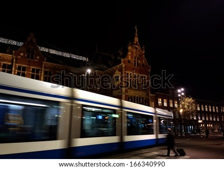 Blue tram in Amsterdam, Netherlands in front of the train station - stock photo