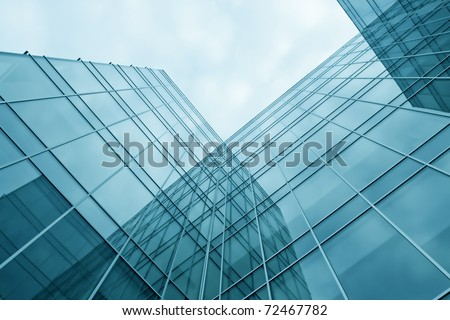 blue transparent textured wall of glass skyscraper in business center - stock photo