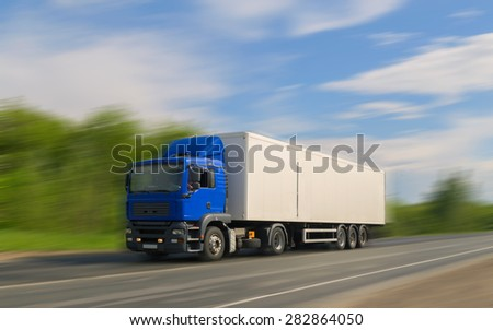 blue truck on asphalt road under blue sky with clouds. - stock photo