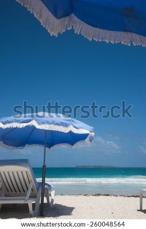 Blue umbrellas above white beach loungers on the white sand beach of Saint Martin - stock photo