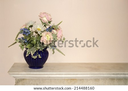 Blue vase full of colorful flowers on a commode - stock photo