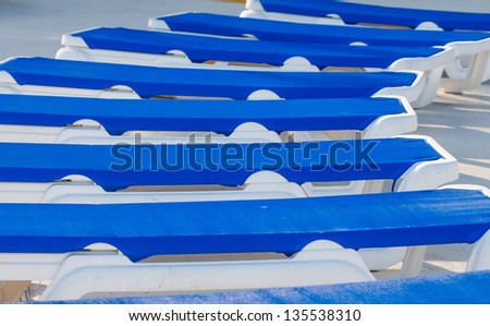 Blue vinyl chaise lounges in a patio around a swimming pool - stock photo