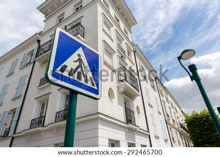 Blue warning road sign with pedestrian symbol in city - stock photo