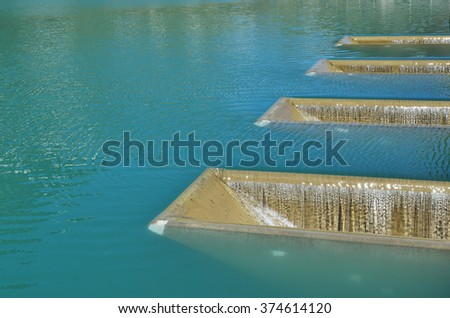 Blue water are shedding through the concrete chutes in the artificial reservoir of the hydroelectric power station. - stock photo