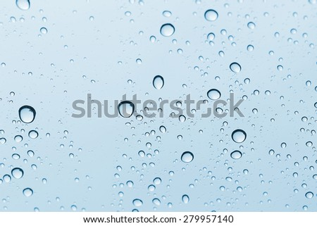 Blue Water drop on glass mirror background. - stock photo