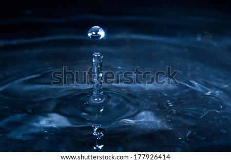 Blue Water drop splash on black background - stock photo