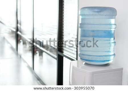 blue water gallon on electric water cooler in office area - stock photo