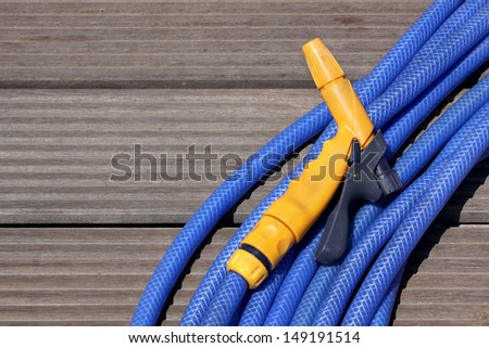Blue water hose with a yellow nosel - stock photo