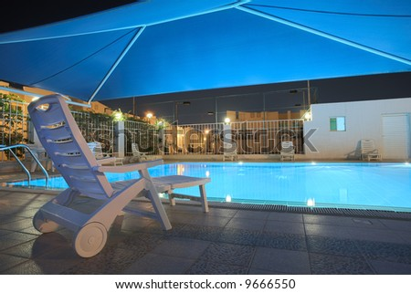 Blue water in a clean swimming pool at night. The pool is covered with a blue shade net roof ? HDR type image - stock photo