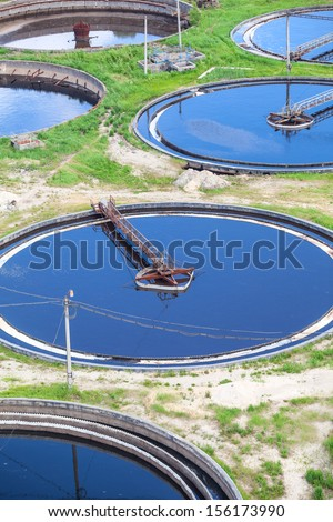Blue water in an industrial wastewater treatment circular settlers, aerial view - stock photo
