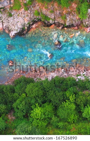 Blue water stream flowing at the bottom of a canyon - stock photo