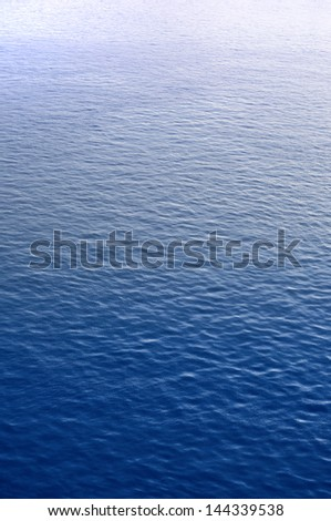 Blue water surface with brightness in the distance - stock photo