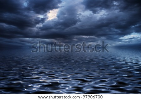 Blue water surface with the reflection of the dramatic clouds